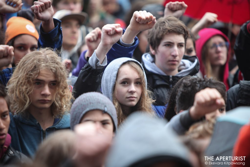 Students raise their fists in solidarity as they gather in front of San Francisco City Hall to protest against gun violence on the one-month anniversary of the high school shooting that a gunman killed 17 people at Marjory Stoneman Douglas High School in Parkland, Florida, Wednesday, March 14, 2018, San Francisco, Calif. (Photo by Ekevara Kitpowsong)