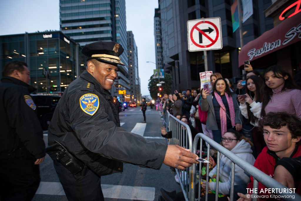 San Francisco Police Chief William Scott hands out the stickers to the crowd during San Francisco's Chinese New Year Parade on Saturday, Feb. 23, 2019. (Photo by Ekevara Kitpowsong/Current SF)