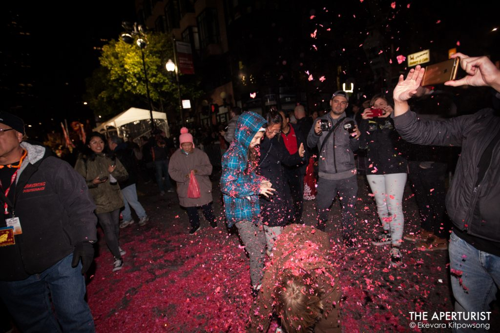 People throw red papers from fireworks in the air during San Francisco's Chinese New Year Parade on Saturday, Feb. 23, 2019. (Photo by Ekevara Kitpowsong/Current SF)