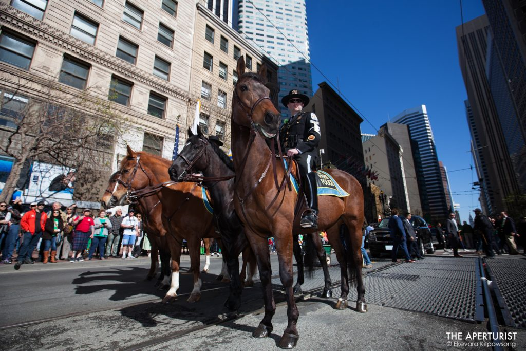 San Francisco police officers ride horses on Market Street during the St. Patrick's Day Parade on Saturday, March 16, 2019, in San Francisco, Calif. (Photo by Ekevara Kitpowsong/Current SF)