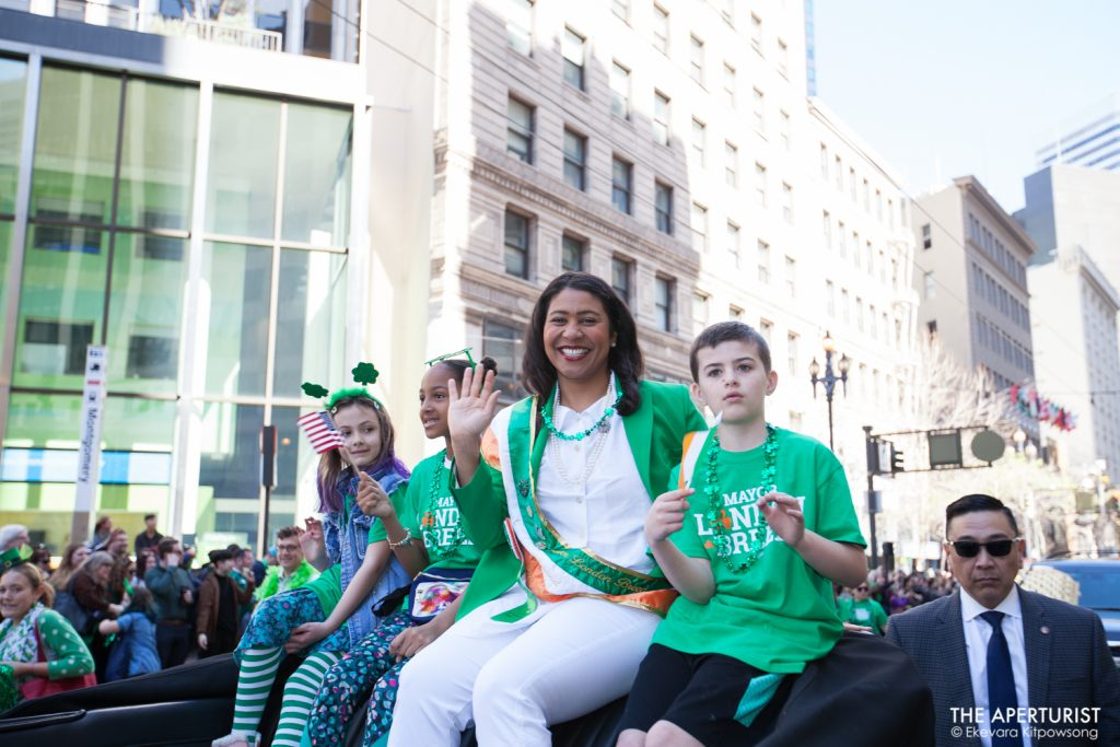 The Grand Marshal of the parade this year San Francisco Mayor London Breed smiles and waves to the crowd on Market Street during the 168th annual San Francisco St. Patrick's Day Parade on Saturday, March 16, 2019. (Photo by Ekevara Kitpowsong/Current SF)