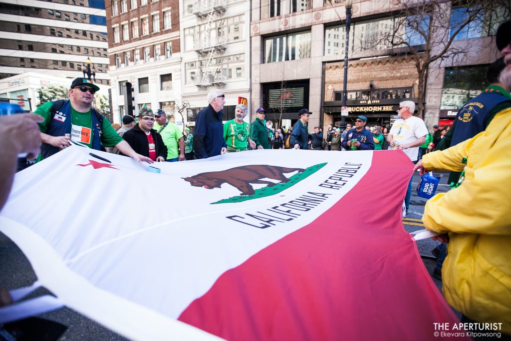 Participants carry a California State flag as they march down Market Street in San Francisco during the 168th annual San Francisco St. Patrick's Day Parade on Saturday, March 16, 2019. (Photo by Ekevara Kitpowsong/Current SF)