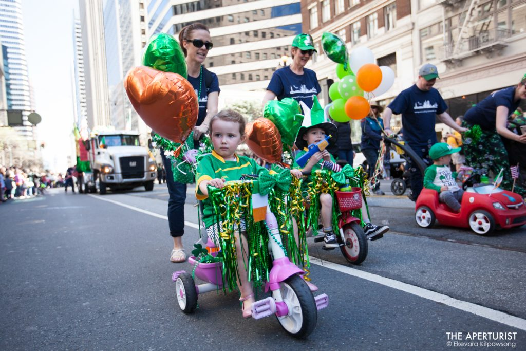 Children ride tricycles on Market Street during the 168th annual San Francisco St. Patrick's Day Parade on Saturday, March 16, 2019, in San Francisco, Calif. (Photo by Ekevara Kitpowsong/Current SF)