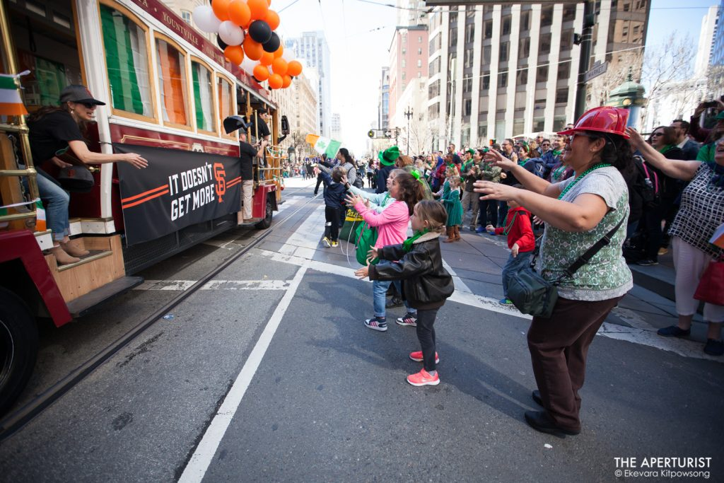 Participants in a cable car throw hats and backpacks to the crowd on Market Street during the 168th annual San Francisco St. Patrick's Day Parade on Saturday, March 16, 2019, in San Francisco, Calif. (Photo by Ekevara Kitpowsong/Current SF)