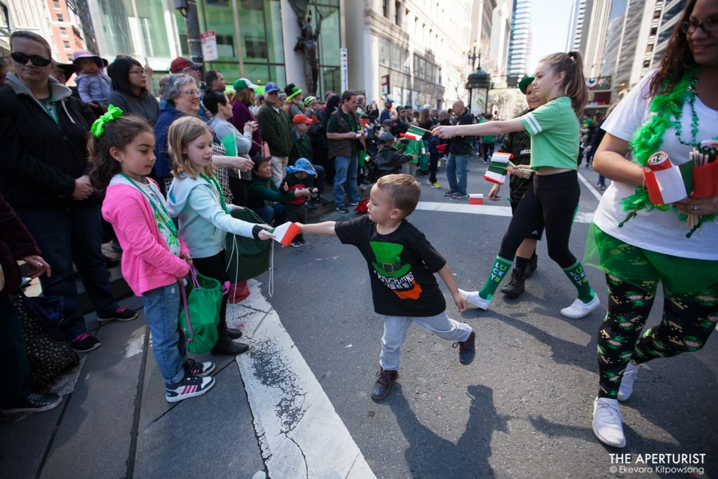 Participants hand out small Irish flags to the parade watchers on Market Street during the 168th annual San Francisco St. Patrick's Day Parade on Saturday, March 16, 2019, in San Francisco, Calif. (Photo by Ekevara Kitpowsong/Current SF)