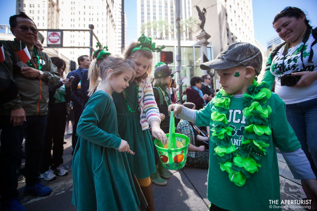 A boy hands out candies in a bucket to two girls on Market Street during the 168th annual San Francisco St. Patrick's Day Parade on Saturday, March 16, 2019, in San Francisco, Calif. (Photo by Ekevara Kitpowsong/Current SF)