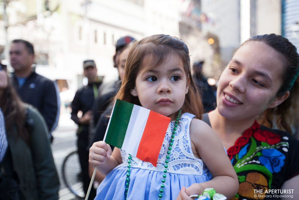 A little girl holds an Irish flag as she enjoys watching the 168th annual San Francisco St. Patrick's Day Parade on Market Street in San Francisco on Saturday, March 16, 2019. (Photo by Ekevara Kitpowsong/Current SF)