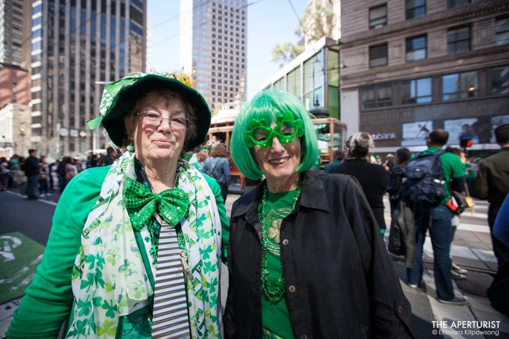 Two women wear green outfits as they walk on Market Street during the 168th annual San Francisco St. Patrick's Day Parade on Saturday, March 16, 2019, in San Francisco, Calif. (Photo by Ekevara Kitpowsong/Current SF)