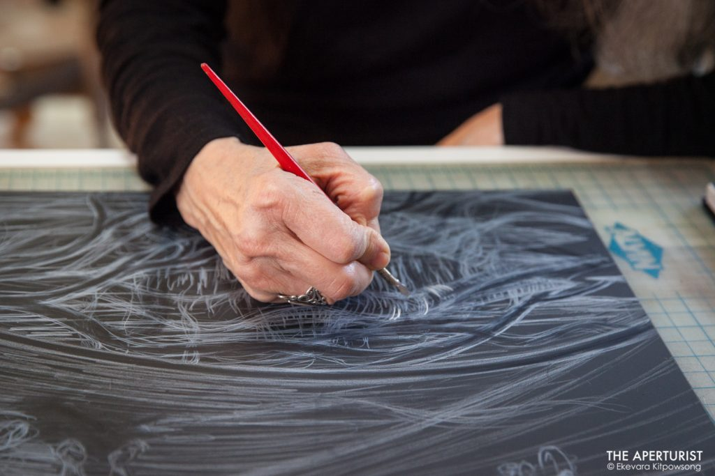"A muralist Juana Alicia works on the scratchboard illustration for ""La X' tabay,"" a book written by Tirso Araiza in her Berkeley studio on Monday, April 29, 2019. (Photo by Ekevara Kitpowsong/Current SF)"
