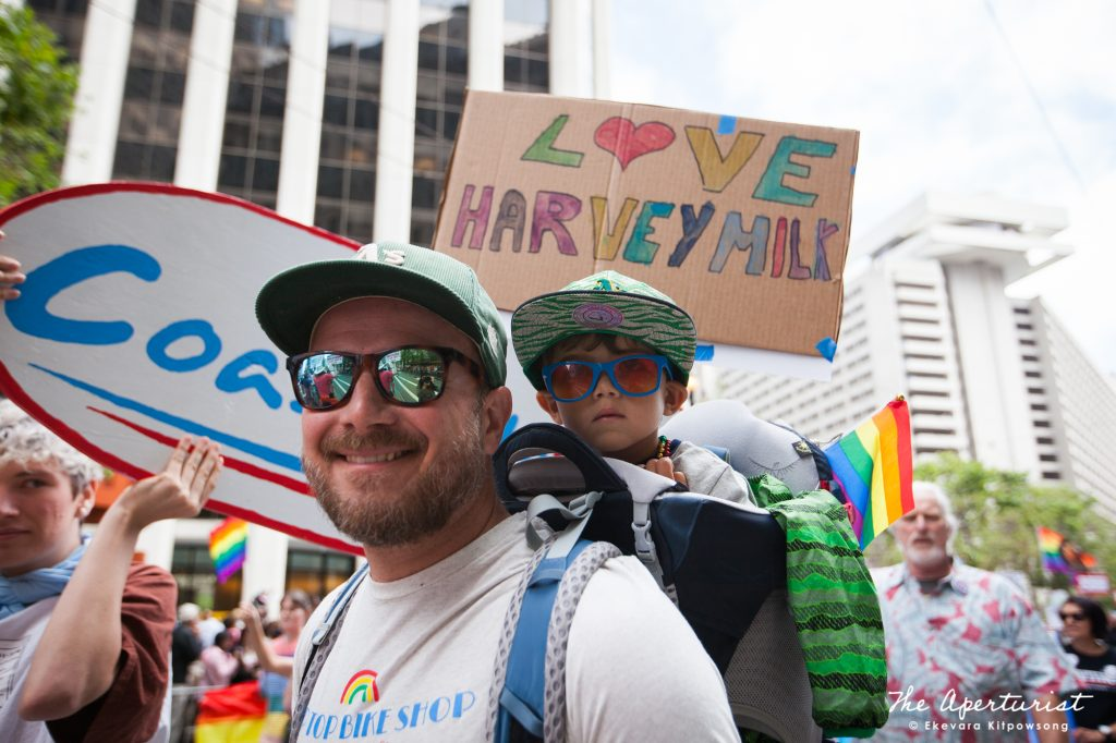 A parade participant carries a child on his shoulder as he marches along Market Street in San Francisco during the San Francisco Pride Parade on Sunday, June 30, 2019. (Photo by Ekevara Kitpowsong/Current SF)