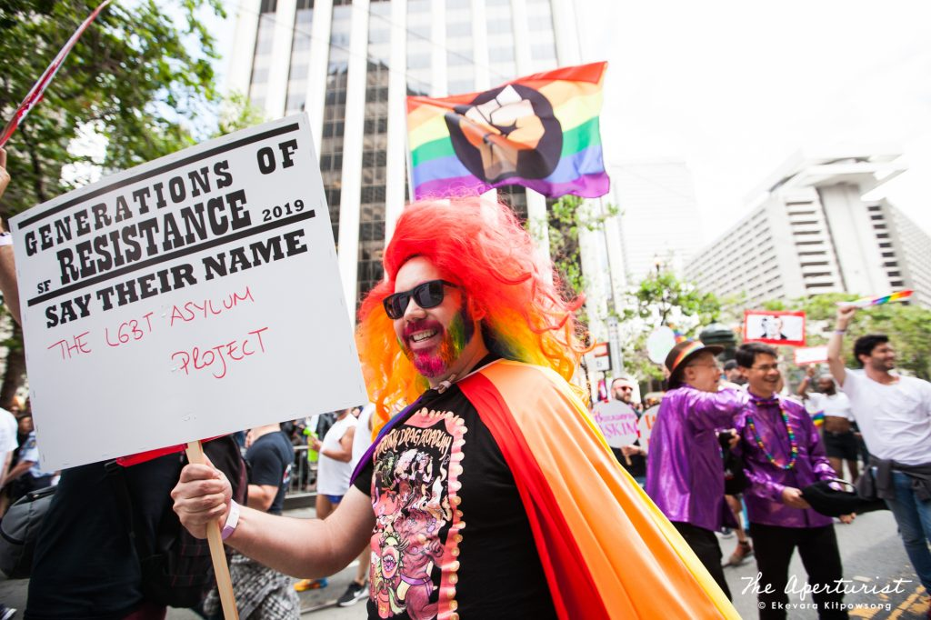 A parade participant holds a banner on Market Street in San Francisco during the San Francisco Pride Parade on Sunday, June 30, 2019. (Photo by Ekevara Kitpowsong/Current SF)