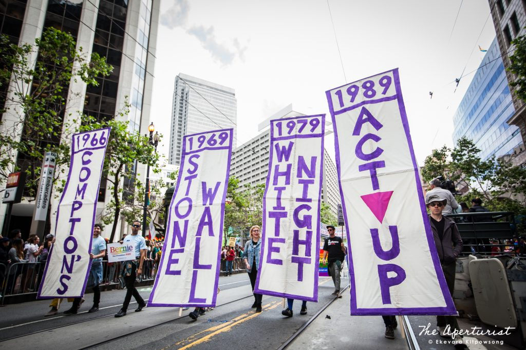 Parade participants hold the Compton's, Stone Wall, White Night and ACT UP banners as they march along Market Street in San Francisco during the San Francisco Pride Parade on Sunday, June 30, 2019. (Photo by Ekevara Kitpowsong/Current SF)