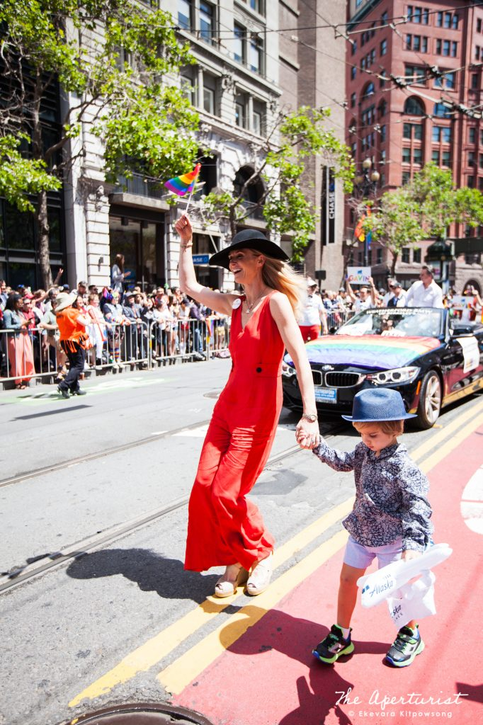 California's First Partner Jennifer Siebel Newsom dances as she holds her son's hand and waves a rainbow flag on Market Street in San Francisco during the San Francisco Pride Parade on Sunday, June 30, 2019. (Photo by Ekevara Kitpowsong/Current SF)
