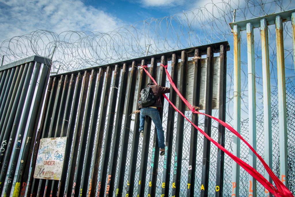 Juan Manuel Barragan Corona, distraught and intoxicated after being recently deported, descends the U.S./Mexico border wall after tying red ribbons on the beams of the border wall as a way to cope with the separation from his children, who remain in the U.S., Sunday, March 10, 2019. (Photo by Mabel Jiménez)