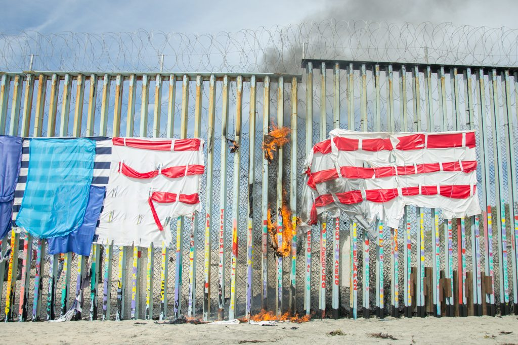 An American flag made up of strips of fabric and set up on the Mexican side of the border wall by migrant caravaners months ago, burns after being set on fire by a local beachgoer on Friday, March 15, 2019 at Playas de Tijuana, the westernmost section of the U.S./Mexico border wall. (Photo by Mabel Jiménez)