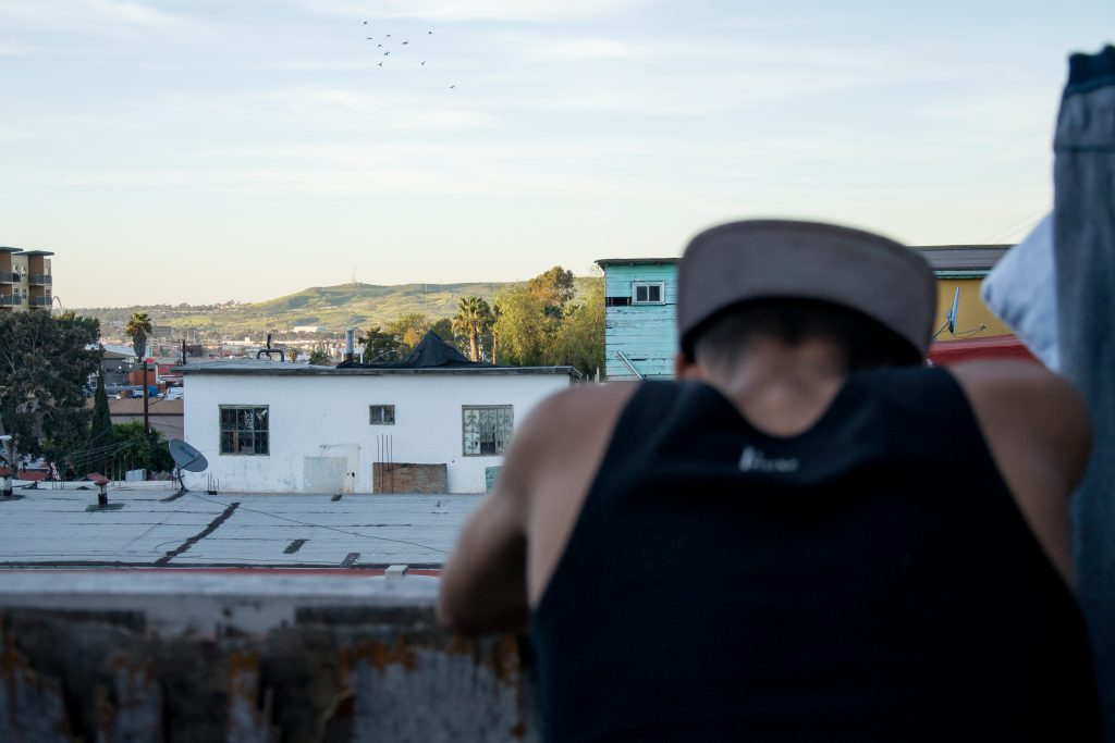 Jenri Jose Juarez Villegas, a 16-year-old refugee from El Salvador, notices a patch of green U.S. soil visible amongst the Tijuana skyline from the backyard of Jardín de las Mariposas, an LGBT drug and alcohol recovery center that recently started opening its doors to LGBT refugees, March 15, 2019. Juarez fled El Salvador after gangs kidnapped his younger sister and threatened his parents. After paying a ransom, his sister was returned, heavily bruised. All his family members fled separately and he does not know any of their whereabouts, or whether they are alive. (Photo by Mabel Jiménez)