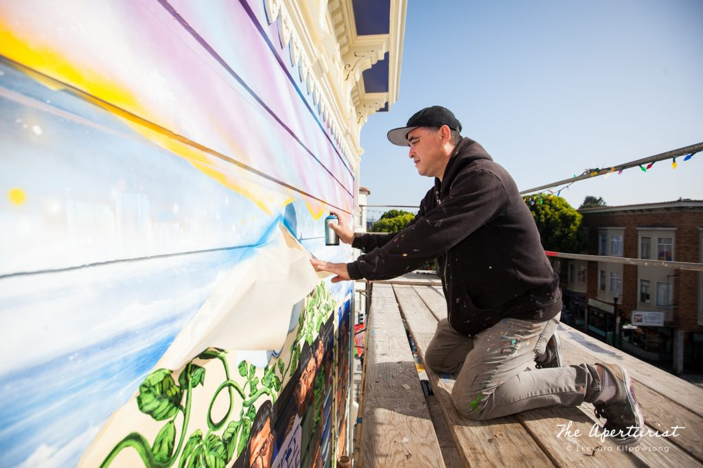 A muralist Cristian Muñoz works on the Justice4Amilcar mural, Alto al Fuego en La Misón, on 24th and Capp streets in the Mission District, San Francisco on Saturday, Nov. 9, 2019. (Photo by Ekevara Kitpowsong/Current SF)