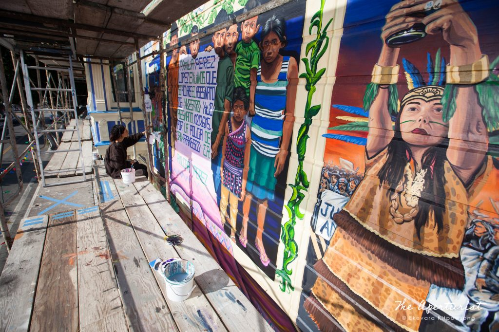A muralist Adrianna Adams works on the Justice4Amilcar mural, Alto al Fuego en La Misón, on 24th and Capp streets in the Mission District, San Francisco on Saturday, Nov. 9, 2019. (Photo by Ekevara Kitpowsong/Current SF)