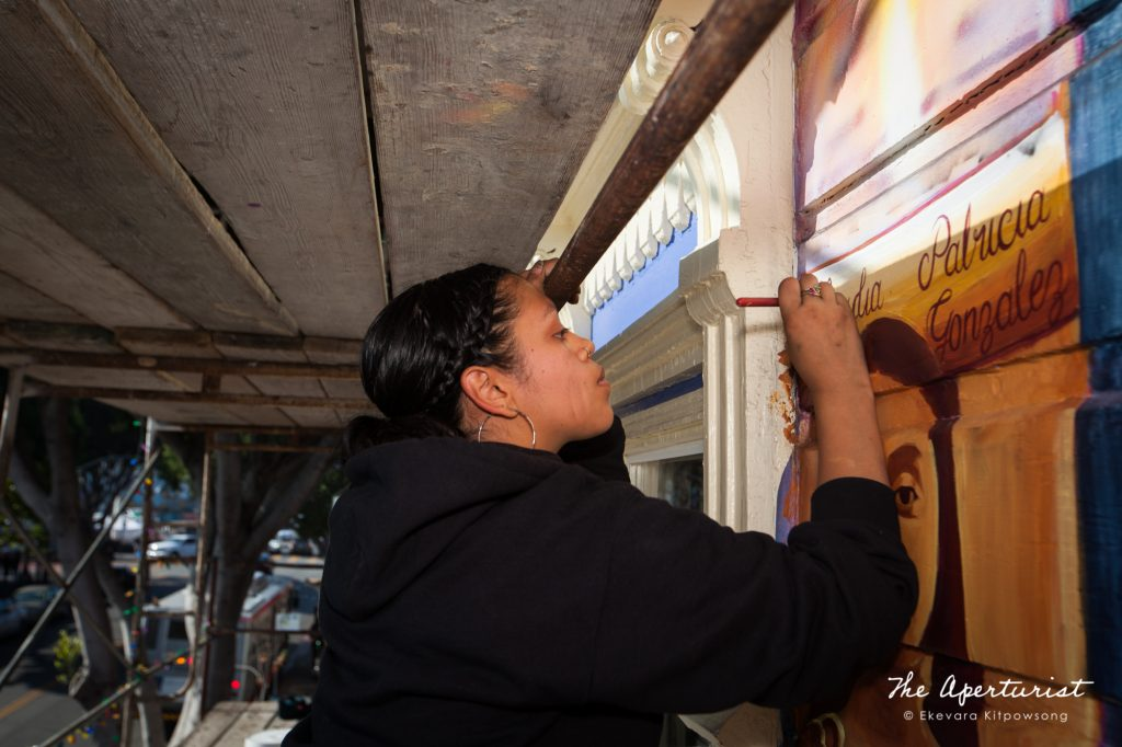"A muralist ""G"" Sonia G Molina works on the Justice4Amilcar mural, Alto al Fuego en La Misón, on 24th and Capp streets in the Mission District, San Francisco on Saturday, Nov. 9, 2019. (Photo by Ekevara Kitpowsong/Current SF)"