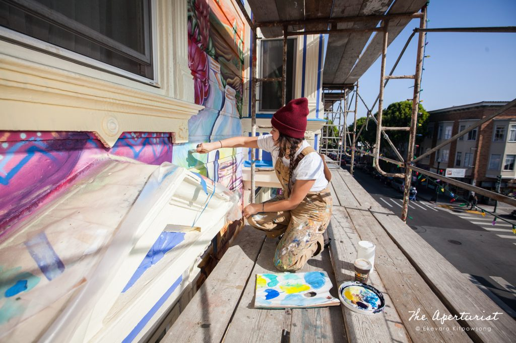 A muralist Flavia Elisa Mora works on the Justice4Amilcar mural, Alto al Fuego en La Misón, on 24th and Capp streets in the Mission District, San Francisco on Saturday, Nov. 9, 2019. (Photo by Ekevara Kitpowsong/Current SF)