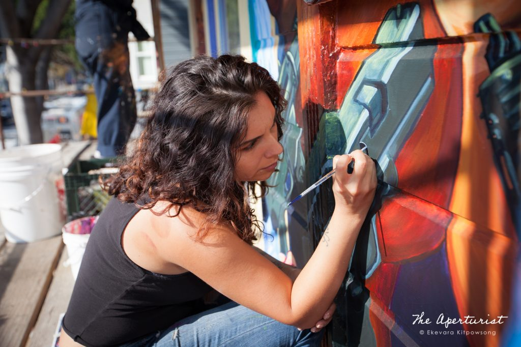 A muralist Lucía González Ippolito works on The Justice4Amilcar Mural, Alto al Fuego en La Misón, on 24th and Capp streets in the Mission District, San Francisco on Sunday, Nov. 10, 2019. (Photo by Ekevara Kitpowsong/Current SF)