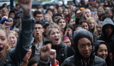 Students raise their fists and chant in solidarity as they gather in front of San Francisco City Hall to protest against gun violence on the one-month anniversary of the high school shooting that a gunman killed 17 people at Marjory Stoneman Douglas High School in Parkland, Florida, Wednesday, March 14, 2018, San Francisco, Calif. (Photo by Ekevara Kitpowsong/Current SF)