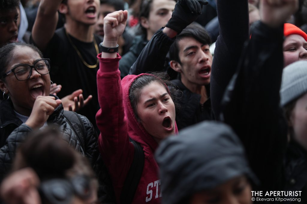 Students raise their fists and chant in solidarity as they gather in front of San Francisco City Hall to protest against gun violence on the one-month anniversary of the high school shooting that a gunman killed 17 people at Marjory Stoneman Douglas High School in Parkland, Florida, Wednesday, March 14, 2018, San Francisco, Calif. (Photo by Ekevara Kitpowsong)
